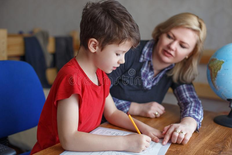 Mother helps son writing homework stock photo