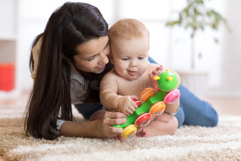 Mom and her baby son play with toy in cosy children room royalty free stock photos