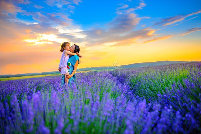 Mother with her beloved daughter walks in the field of lavender royalty free stock photo