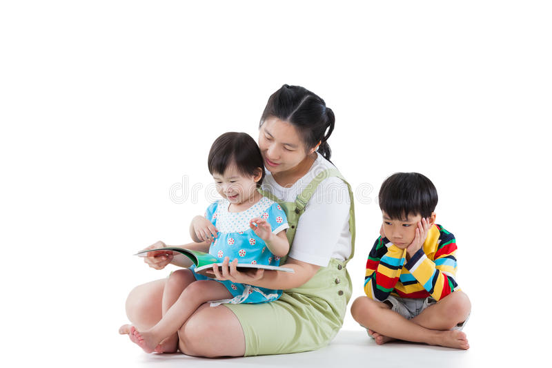 Mother with her child, daughter reading a book, son feel bad (different gesture). Isolated on white royalty free stock photography