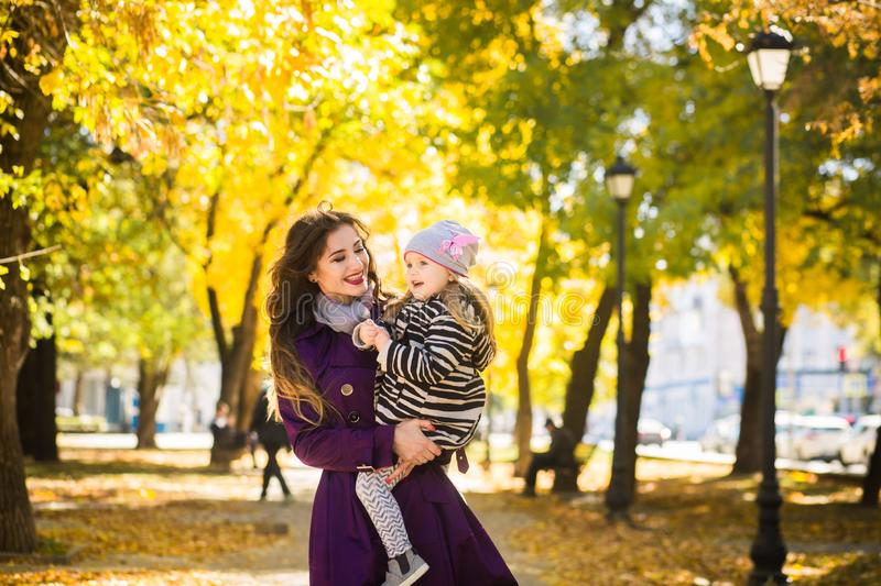 Mother and her child girl playing together on autumn walk in nature outdoors. Young mother and her child girl playing together on autumn walk in nature outdoors royalty free stock photography