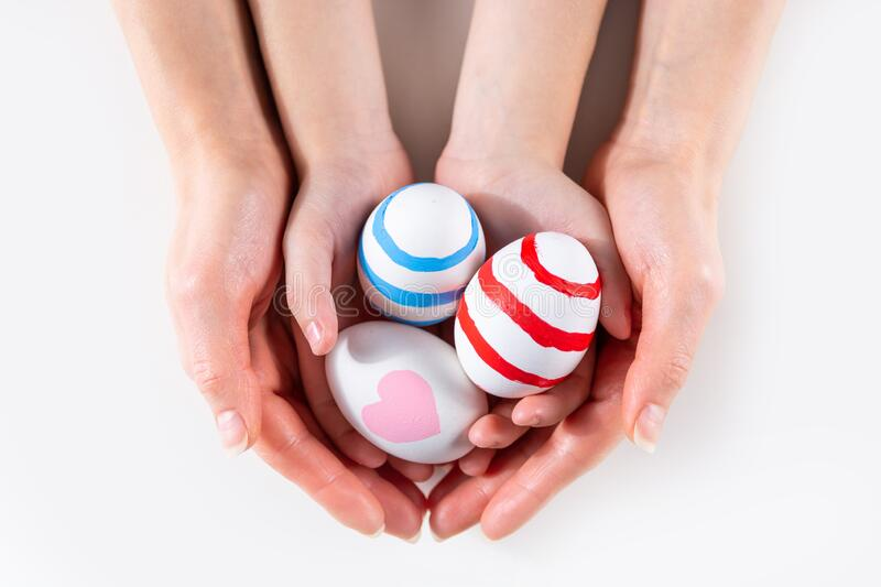 Mother and her child hands holding painting Easter eggs stock images
