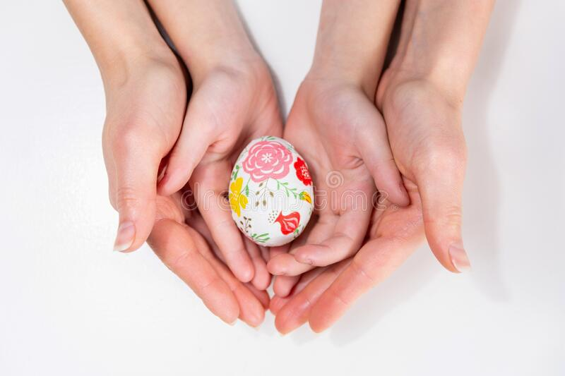 Mother and her child hands holding painting Easter eggs royalty free stock photos