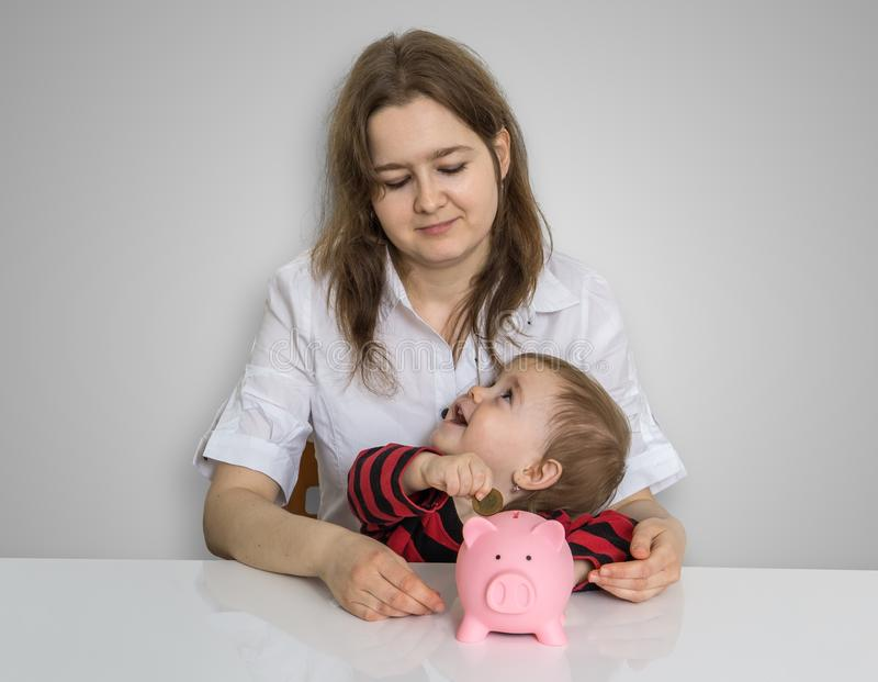 Mother and her child are holding piggy bank with savings royalty free stock photos