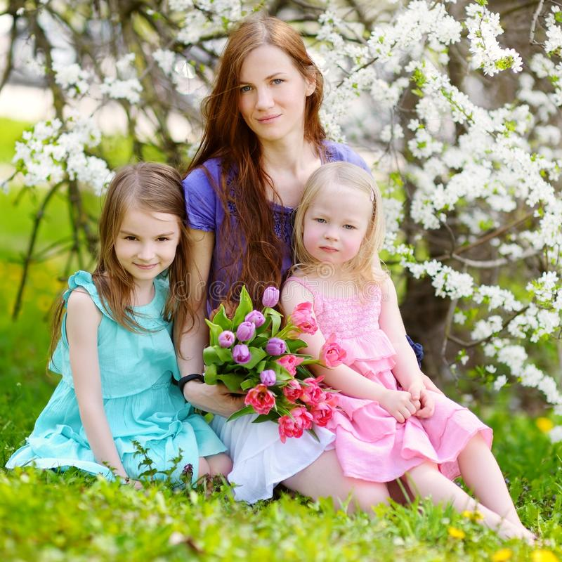 Mother and her children in blooming cherry garden stock images