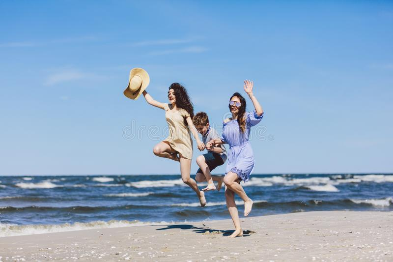 Mother and her children jumping high on the beach. royalty free stock image