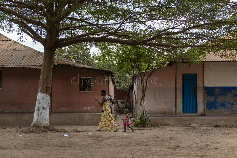 A mother with her children walking at a dirt street in the city of Bissau, in Guinea-Bissau. Bissau, Republic of Guinea-Bissau - February 8, 2018: A mother with royalty free stock image
