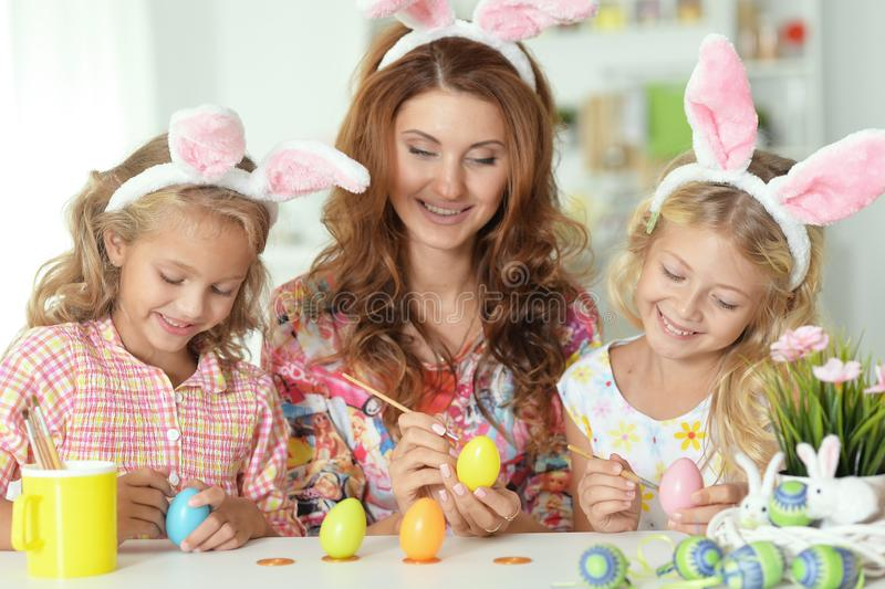 Mother with her cute daughters wearing rabbit ears and painting Easter eggs royalty free stock photos
