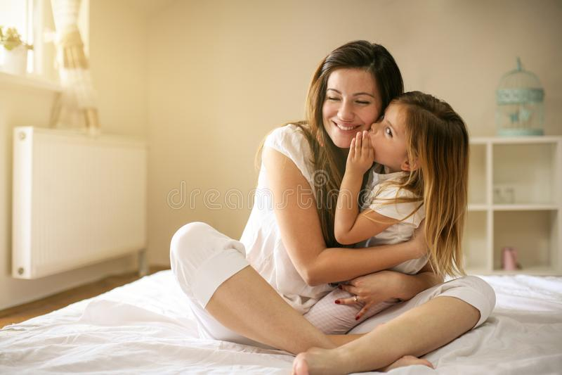 Mother with her cute little daughter lying on bed. stock images