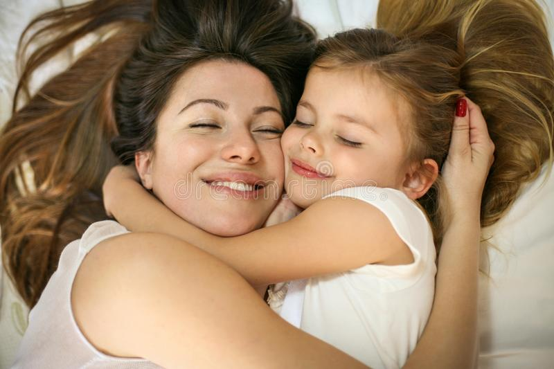 Mother and daughter in the bed together. stock photo