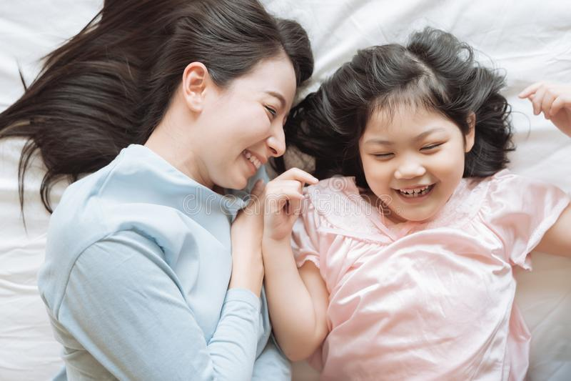 Mother and her daughter child girl hugging her mom in the bedroom .Happy Asian family. royalty free stock photos