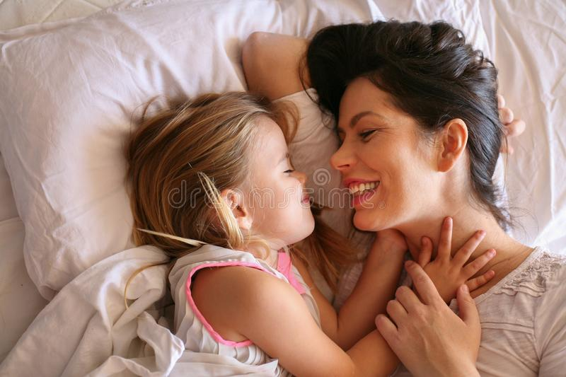 Mother and daughter laying in bed. royalty free stock photography