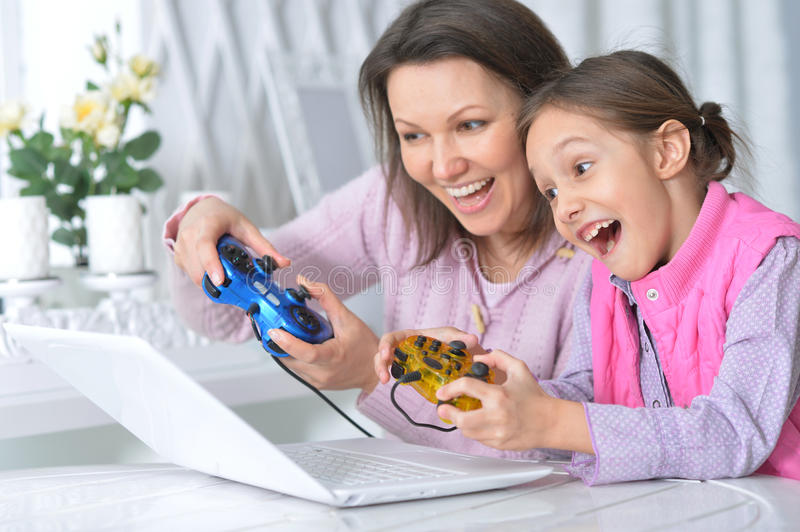 Mother with her daughter enjoying a laptop stock photo