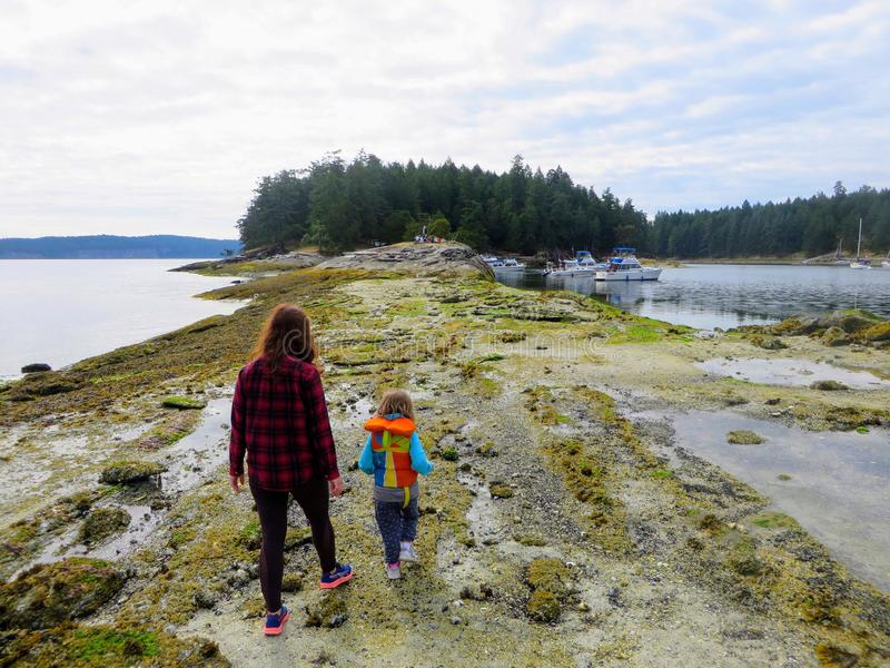 A mother and her daughter exploring the tidal pools and shores of the gulf islands of british columbia, Canada. They are looking for sea creatures during low royalty free stock photo