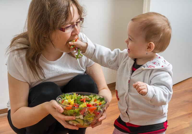 Mother and her daughter having fun and playing. Little child is feeding her mother with salad royalty free stock photo