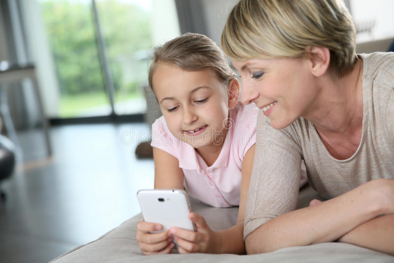 Mother and her daughter at home relaxing stock photography