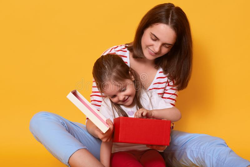 Mother and her daughter opening mommy`s present while sitting on floor. Woman wearing blue trousers and striped casual shirt stock image