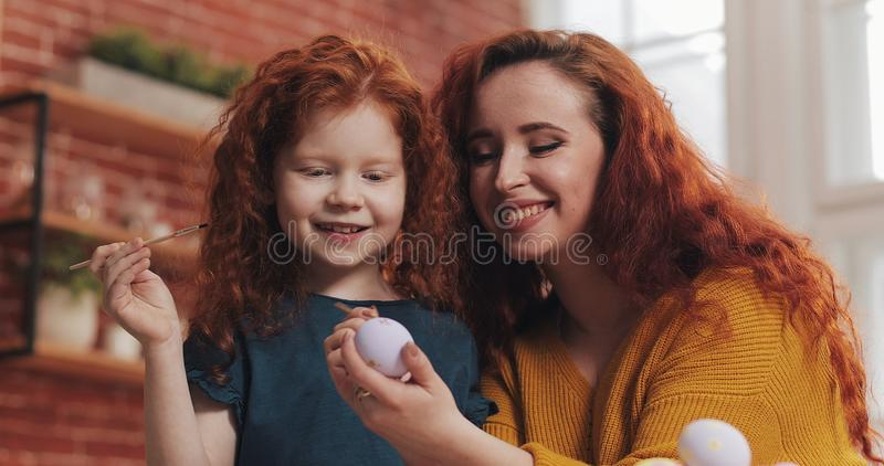 A mother and her daughter painting Easter eggs in cozy kitchen. They laughing and have fun. Happy family preparing for stock photography