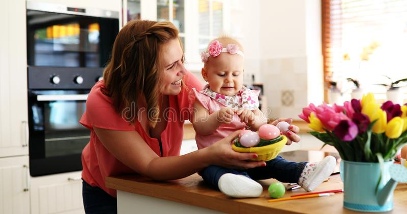 Mother and her daughter painting Easter eggs royalty free stock photos
