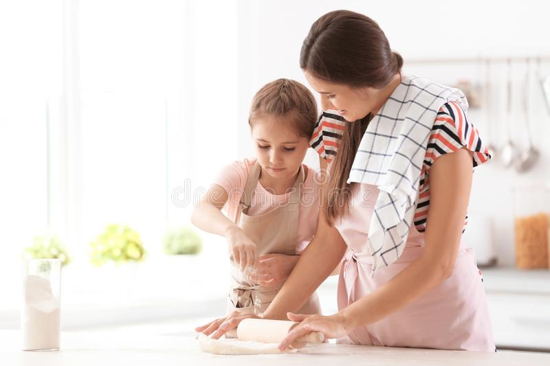 Mother and her daughter preparing dough at table in kitchen stock images