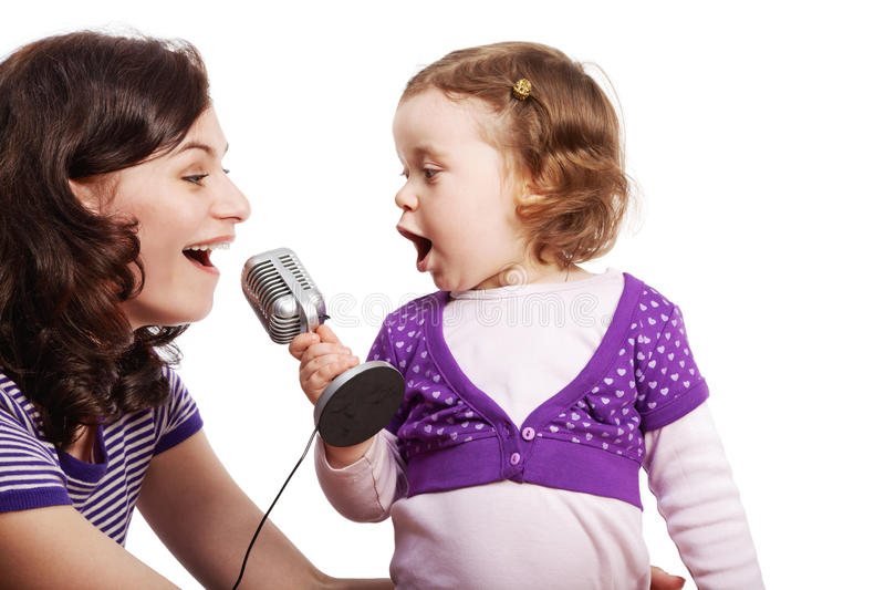 Mother and her daughter sing into microphone stock images