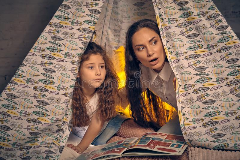 Mother and daughter are sitting in a teepee tent with some pillows and reading stories. Happy family. Mother and her daughter are sitting in a teepee tent with royalty free stock images