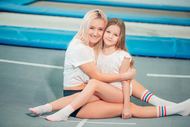 Pretty siters girls having fun indoor. Jumping on trampoline in children zone royalty free stock photography