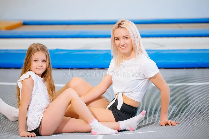 Pretty siters girls having fun indoor. Jumping on trampoline in children zone royalty free stock image