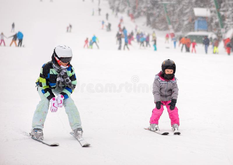 Mother and her daughter skiing stock photo