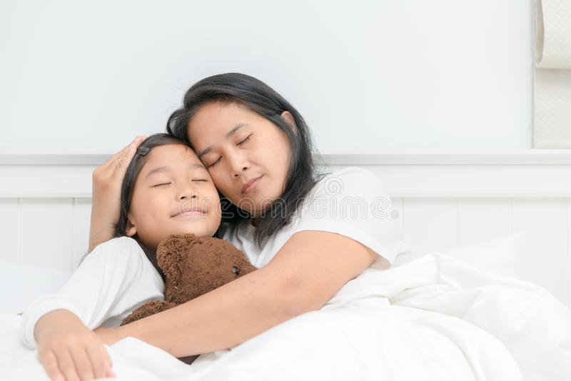 Mother and her daughter sleep on bed together, royalty free stock images