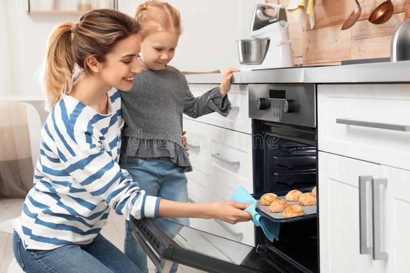 Mother and her daughter taking out cookies from oven royalty free stock image