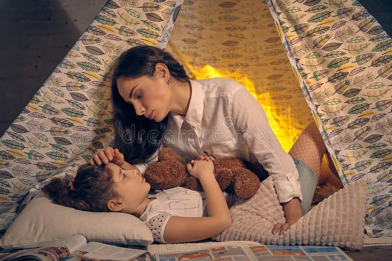 Mother and her daughter are in a teepee tent with some pillows. Happy family. Mother and her daughter are in a teepee tent with some pillows. Girl is lying and stock photo