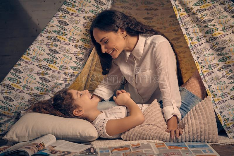 Mother and her daughter are in a teepee tent with some pillows. Happy family. Mother and her daughter are in a teepee tent with some pillows. They are smiling stock photo