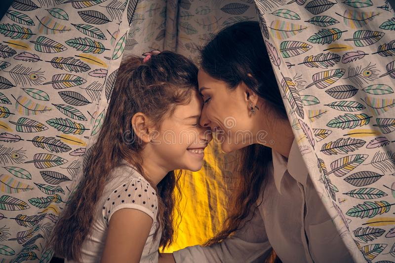 Mother and her daughter are in a teepee tent with some pillows. Happy family. Mother and daughter are sitting in a teepee tent with some pillows, reading stock images