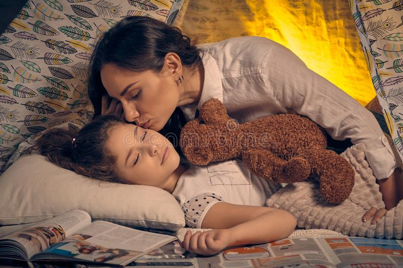 Mother and her daughter are in a teepee tent with some pillows. Happy family. Young mother and her pretty daughter are in a teepee tent with some pillows. Girl royalty free stock image