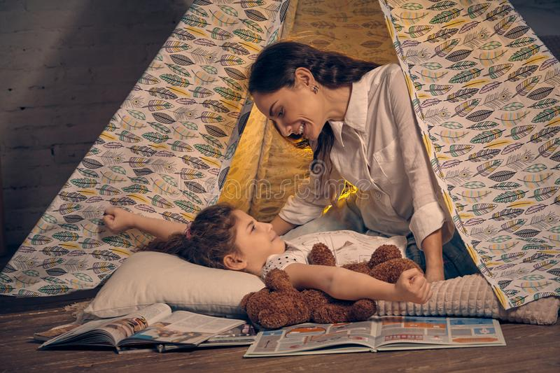 Mother and her daughter are in a teepee tent with some pillows. Happy family. Young mother and her pretty daughter are in a teepee tent with some pillows. Girl stock image