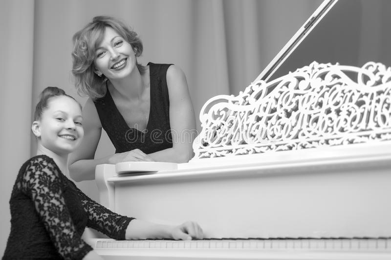Mother with her daughter together at the piano royalty free stock photo
