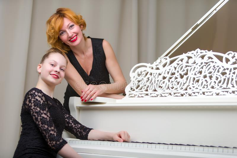Mother with her daughter together at the piano stock photography