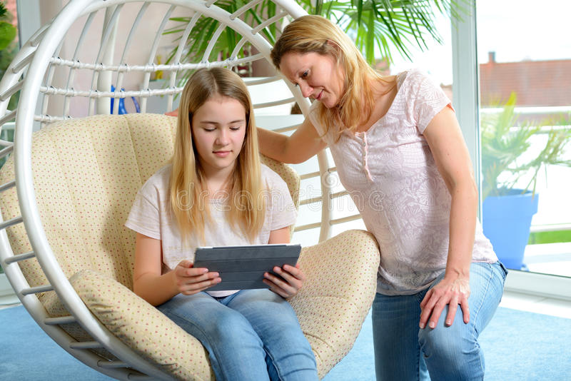 Mother and her daughter using tablet computer together royalty free stock image