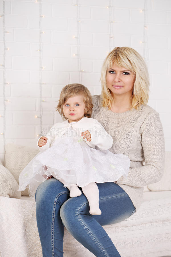 Mother and her daughter on a white bed stock photos