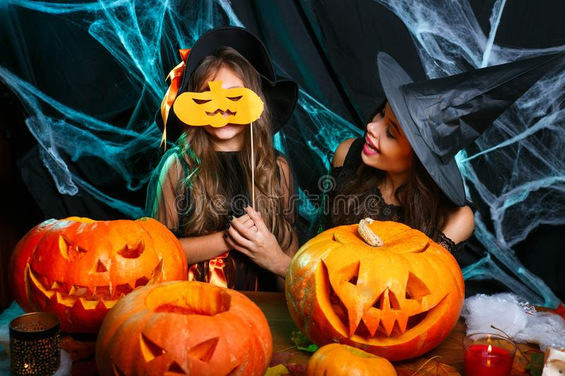 Happy Halloween. Mother and her daughter in witch costumes having fun at home. Mother and her daughter in witch costumes having fun at home. Happy Family royalty free stock photography