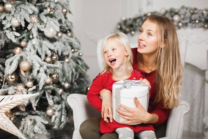 Mother and her daughters opening the little girl`s birthday present royalty free stock photo