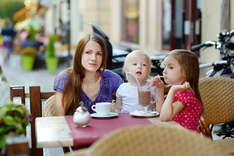 Mother and her daughters relaxing in outdoor cafe stock photo