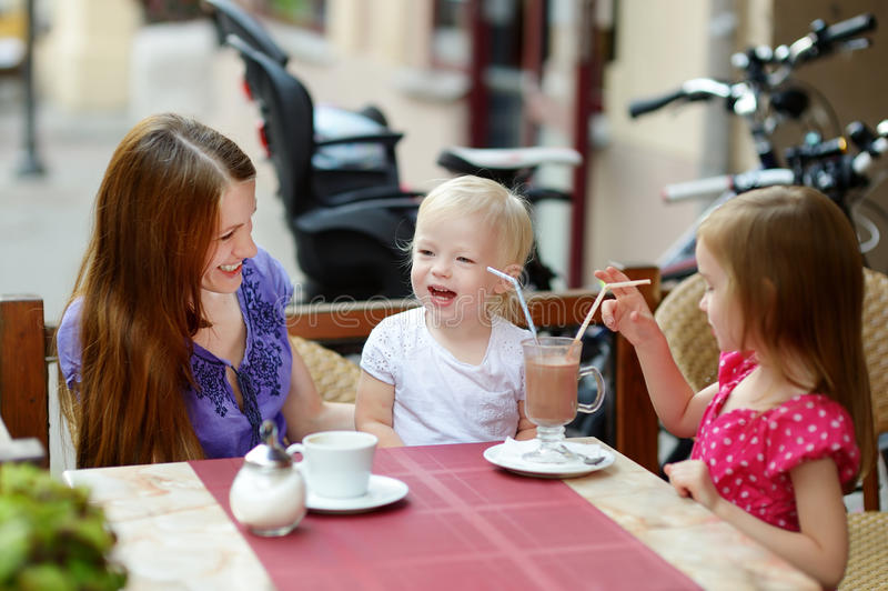 Mother and her daughters relaxing in outdoor cafe stock images