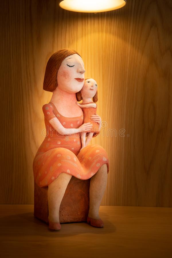 A mother with her eyes closed sitting holding a child stock photos