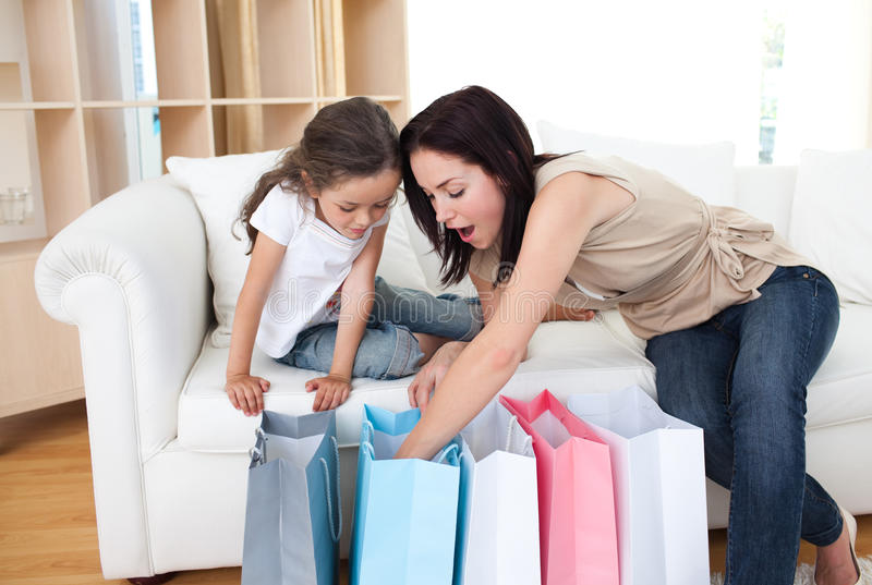 Mother and her girl opening shopping bags royalty free stock photography