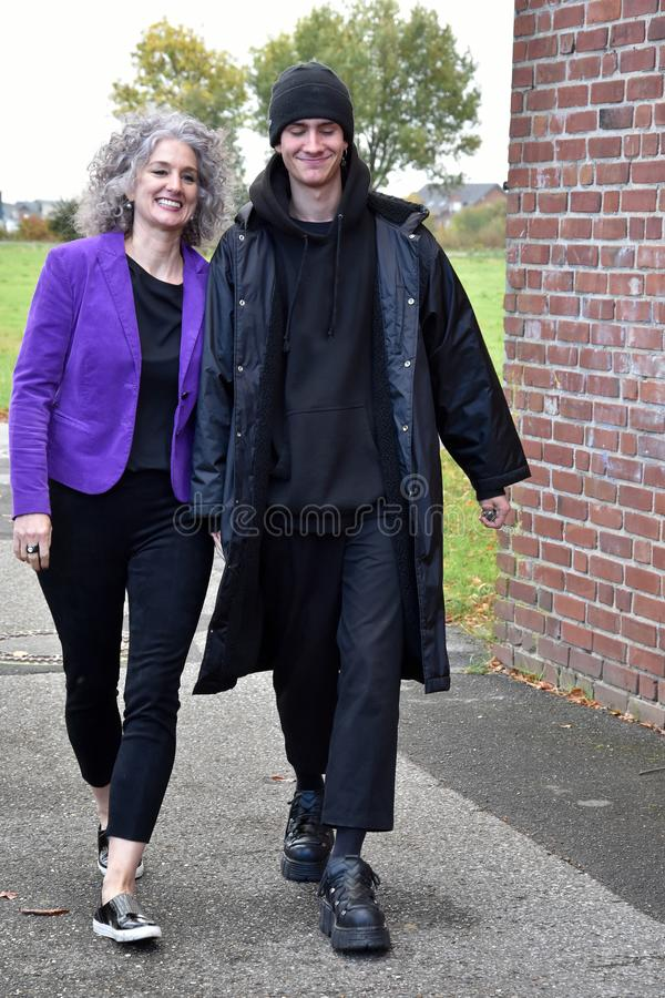 Best friends, mother and teenage son walking hand in hand. Mother and her grown up teenage son are best friends, walking together hand in hand and having fun stock image