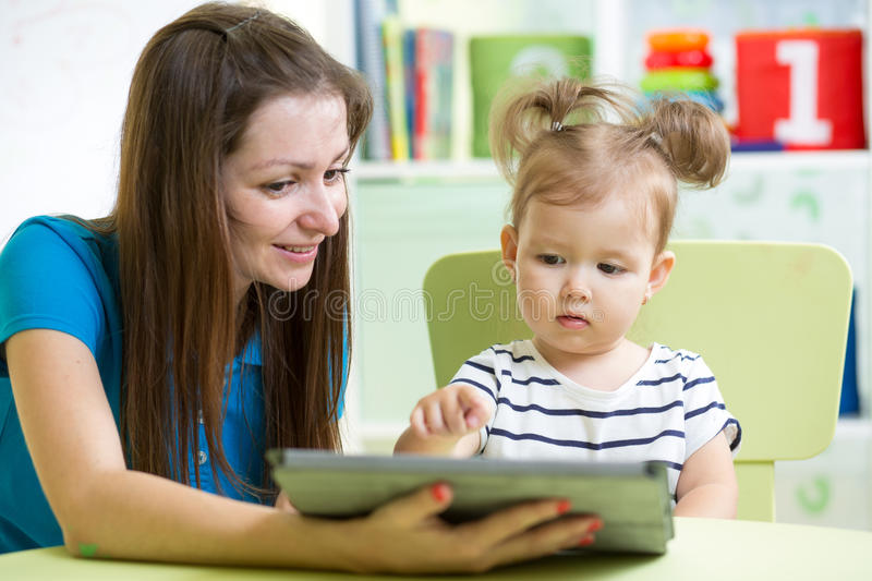 Mother and her kid daughter with tablet pc royalty free stock photography