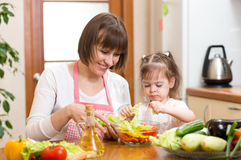 Mother and her kid making vegetable salad royalty free stock images