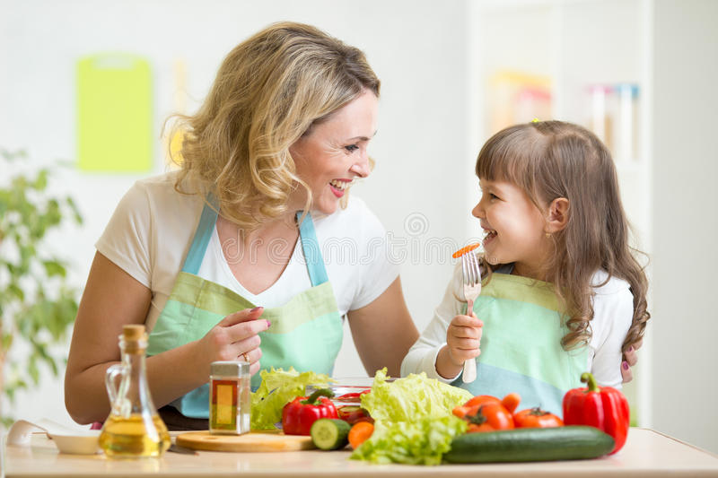 Mother and her kid preparing healthy food and stock photo